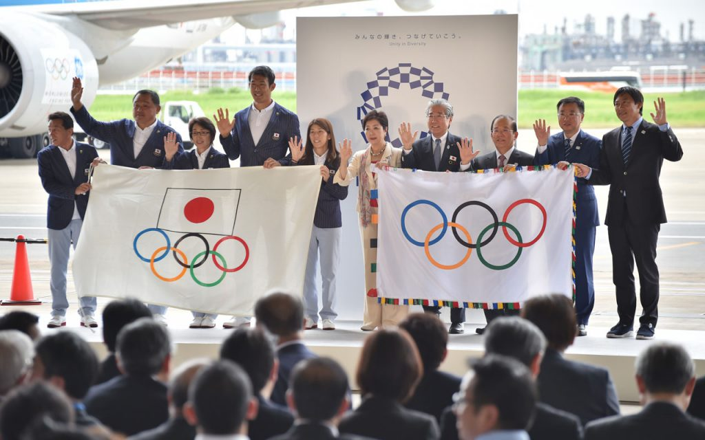 Tokyo governor Yuriko Koike (5th R), Japan Olympic Committee officials and their Rio de Janeiro Olympic squad leaders pose with flags during the offical flag arrival ceremony at the Tokyo's Haneda airport on August 24, 2016. The Olympic flag arrived in Tokyo on August 24, as Japan's capital gears up to host the 2020 Games, with officials promising smooth sailing after Rio's sometimes shaky 2016 instalment. / AFP PHOTO / KAZUHIRO NOGI